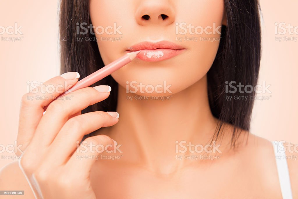 Close up of young woman doing maquillage with lip's liner stock photo