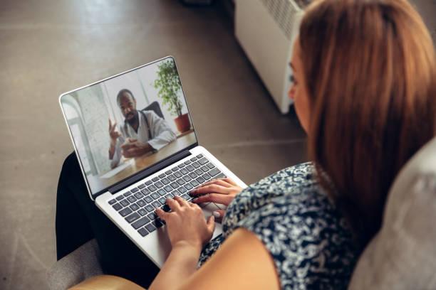 acercamiento de la joven mujer recibiendo ayuda médica en línea y consejos durante videollamada con el médico revisando simtomes aand explicando las reciepes de la droga - telehealth fotografías e imágenes de stock