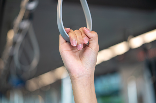 Close up of young woman holding handrail in train
