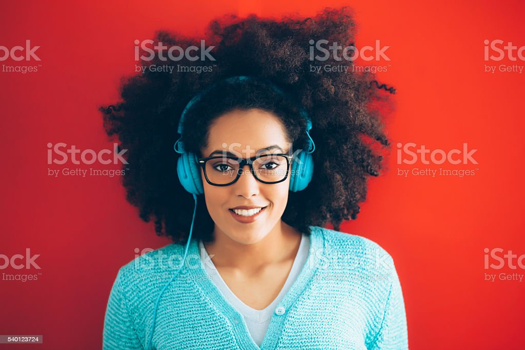 Close up of young woman listening music on red background stock photo