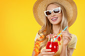 istock Close up of young woman posing isolated over yellow background and drinking cocktail 1202301990