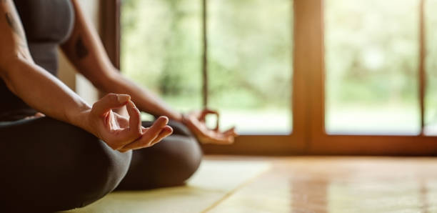 Close up of young woman practicing yoga at home stock photo