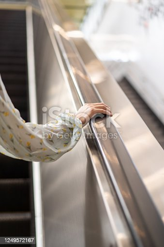 Close up of young woman right hand holding escalator handrail