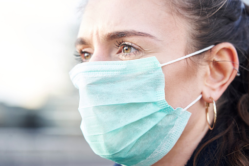 istock Close Up Of Young woman wearing face mask while walking in the streets of London 1210333424