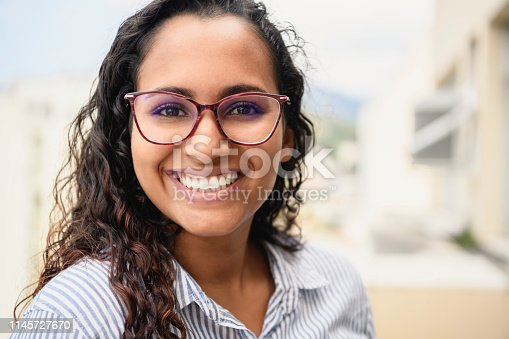 Attractive young woman in her 20s with curly hair, looking towards camera, smiling, carefree