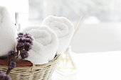 close up ofTowel placed on basket, white table top, bottle of liquid soap, spa set for bathing in the bathroom, copy space, bathroom window.