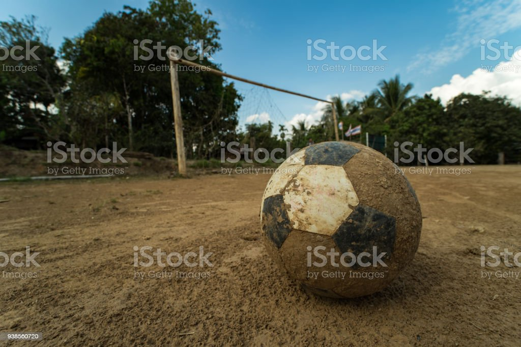 close up old football on ground at a dirt pitch stock photo