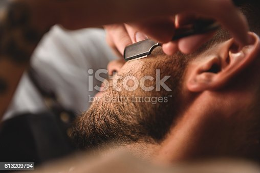 istock close up old razor in hands of specialist 613209794