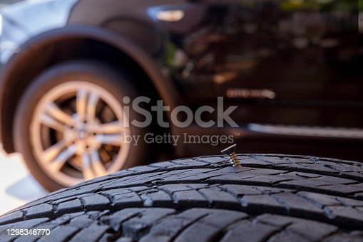 Close up old tire have nails nut or screw drive stuck in side. Tire workshop and change old wheel on the car. Used car tires stacked in piles at tire fitting service repair shop
