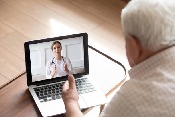 cerrar hombre mayor hablando con el médico en línea, videollamada - telehealth fotografías e imágenes de stock