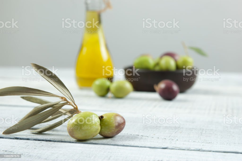Close Up Olive Branch Glass Bottle Of Olive Oil And Wooden Breakfast