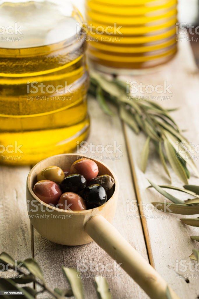 Aceitunas, botella de aceite de oliva y aceite de oliva hojas de cerca. - foto de stock