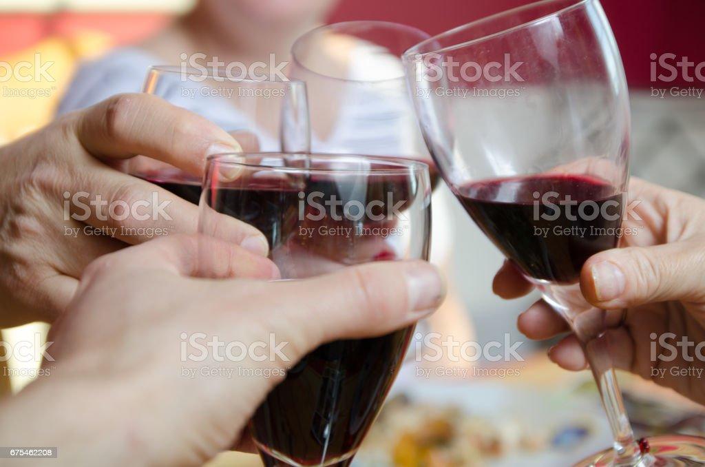 Gros plan sur 4 mains grillage avec verre de vin rouge photo libre de droits