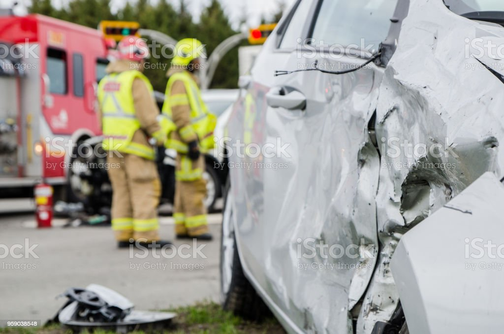 Close up on a car crashed with fireman in background stock photo