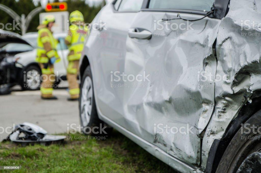 Hautnah auf einem Auto stürzte mit Feuerwehrmann im Hintergrund – Foto