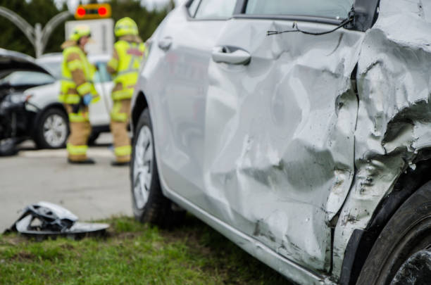 close up on a car crashed with fireman in background - car accident stock photos and pictures