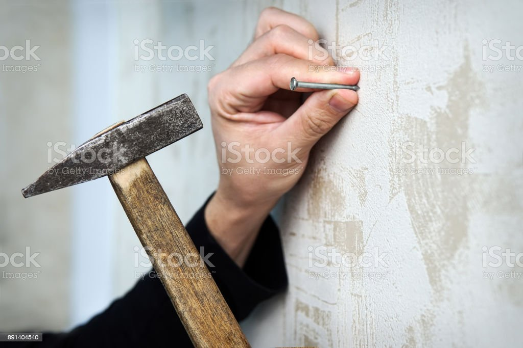 Close up on a hand hammering a nail on a wall stock photo