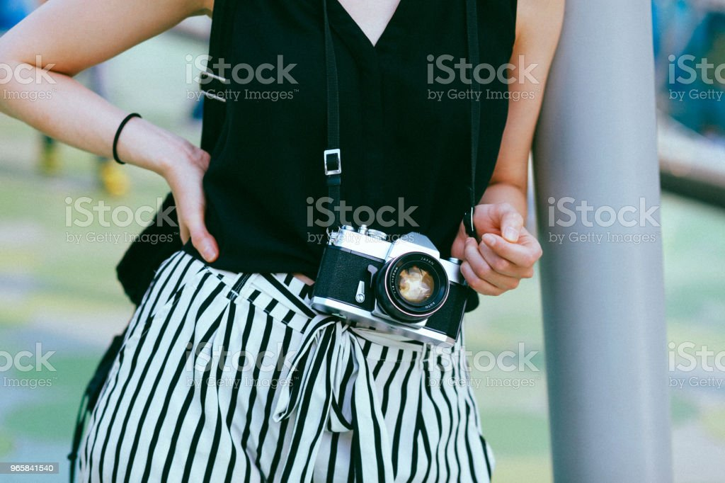 close up on a vintage film camera on a modern young woman close up image of a young woman having a vintage film camera or a modern mirrorless system packed in a stylish silver camera body. Adult Stock Photo
