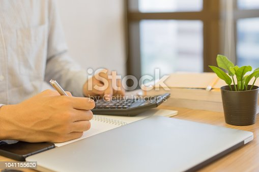 istock close up on accountant employee man hand writing cost estimate and pressing on calculator for calculating price at desk , senior accountant job working concept 1041155620