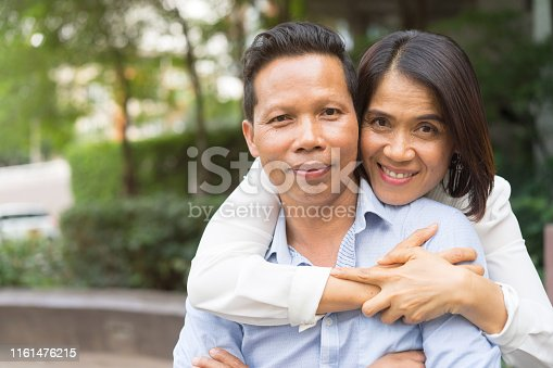 istock close up on asian mature man is embraced by asian woman standing outdoor at public park in weekend day and smiling , couple lover relationship concept 1161476215