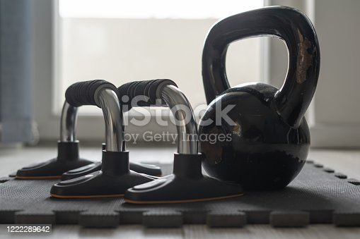 Close up on black kettlebell girya training weight and push up bars on the floor at home in day training equipment