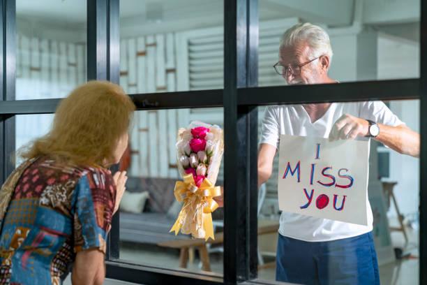 sluit omhoog op boeket. hogere mens die vrouw in quarantaine door venster bezoekt - raam bezoek stockfoto's en -beelden