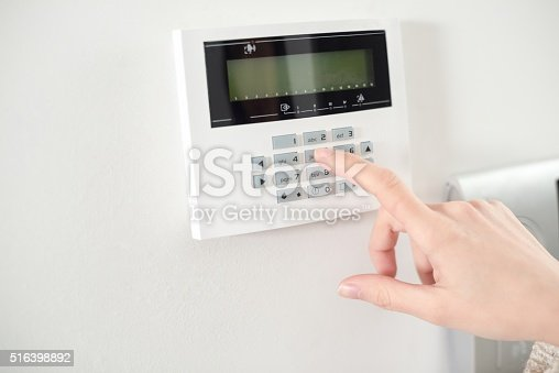 istock Close up on brunette woman's hand entering code 516398892