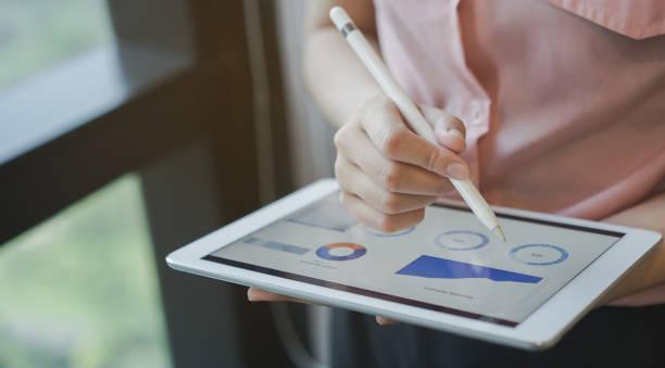 geschäftsfrau manager hand mit stylus-stift für schreiben oder kommentieren sie screen-dashboard-tablette bei der bewältigung der situation über leistung, technologie und business strategie-konzept des unternehmens hautnah - geschäftsstrategie stock-fotos und bilder