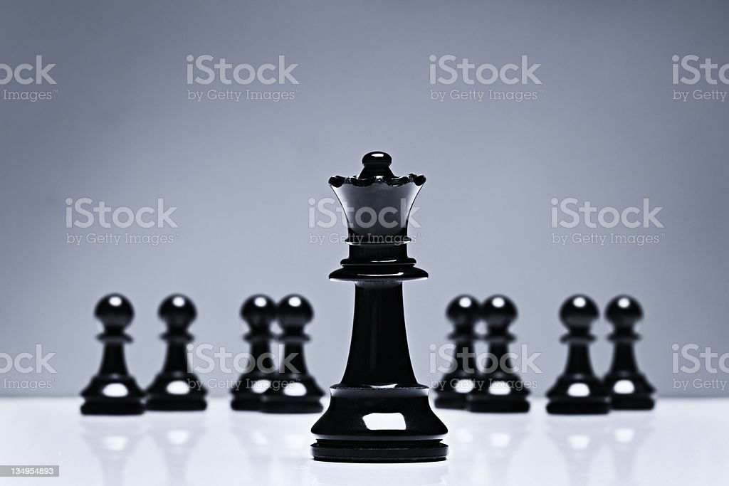 Close up on chess queen against pawns in background stock photo