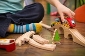 istock Close up on child's hands with toy train and railway in his room. Boy playing indoors. 942498974