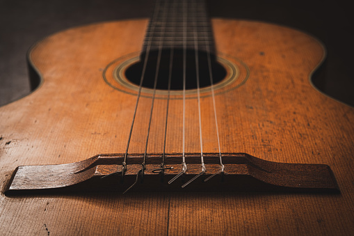 Music background string instrument close up on classic guitar bridge focus on foreground no people