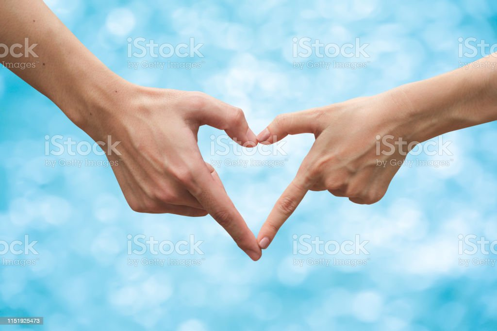 close up on couple human of man and woman hands make heart shape...