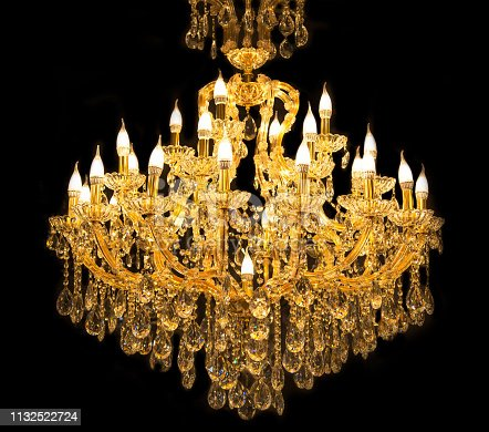 Close up on crystal of contemporary chandelier, is a branched ornamental light fixture designed to be mounted on ceilings or walls. Black background