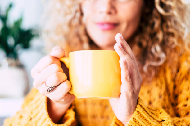 Close up on cup with tea or coffe drink inside and beautiful defocused woman in background - concept of relax and healthy lifestyle with nice people - yellow colors mood stock photo