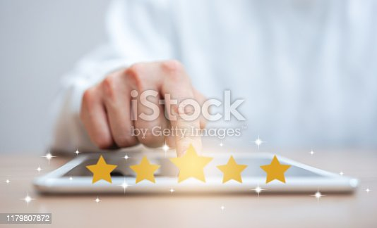 533983044istockphoto close up on customer man hand pressing on digital tablet screen with gold five star rating feedback icon and press level three rank (good) for giving score point to review the service , technology business concept 1179807872