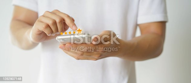 1128693163 istock photo close up on customer man hand pressing on smartphone screen with  five star rating feedback icon and press level excellent rank for giving best score point to review the service , technology business concept 1252907148