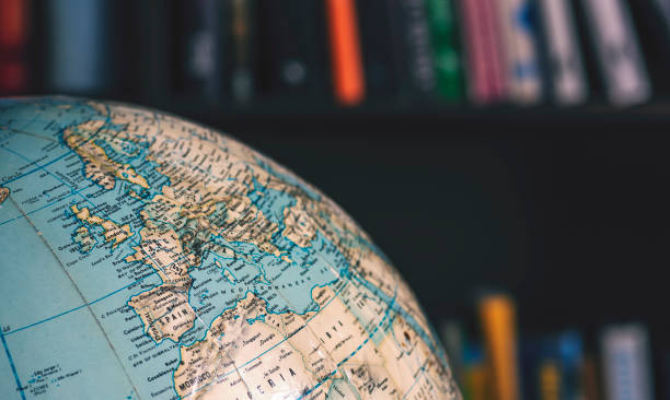 close up on desktop globe. europe and northern africa. in background out of focus books on shelves - europe map stock photos and pictures