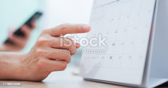 close up on employee man hand using finger pointing schedule (timetable) on calendar to make appointment meeting or manage timetable each day , life balance concept