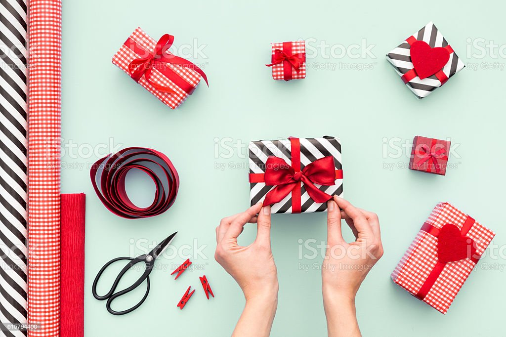Close up on female hands packing presents. Top view. stock photo