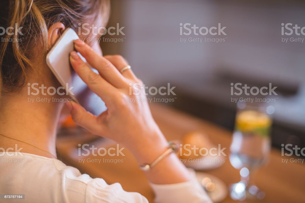 Close up on female using mobile in a cafe shop stock photo