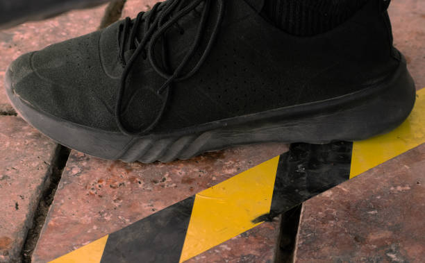 Close up on foot next to marking on the ground and signage for physical or social distancing stock photo