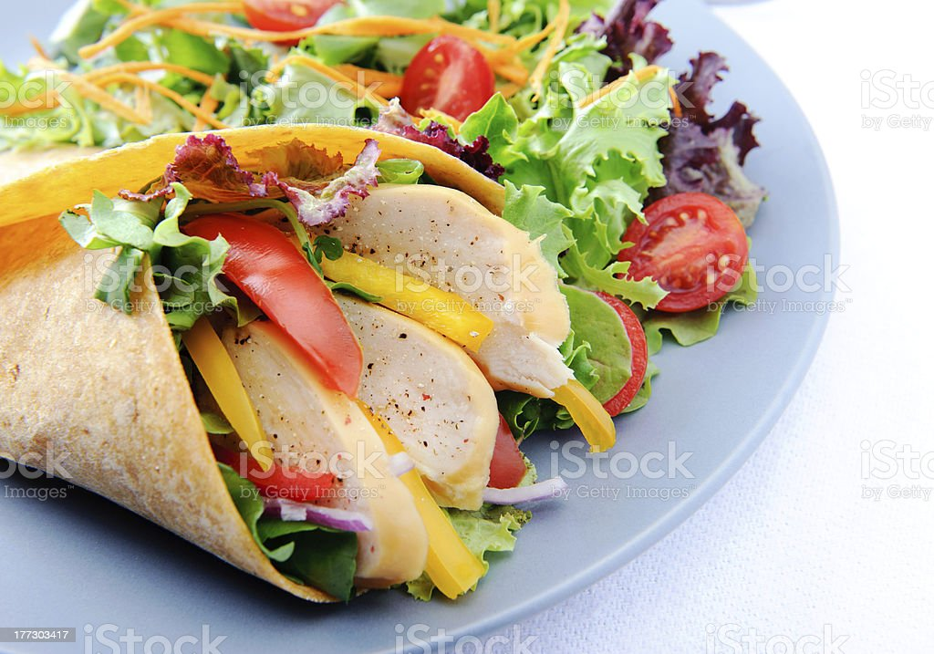 Close up on fresh chicken vegetable wrap with side salad stock photo
