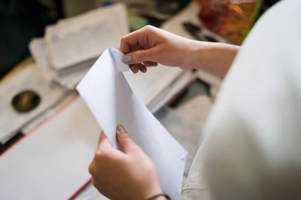 de cerca en la mujer mujer mano sosteniendo y abriendo sobre blanco por la mesa en el trabajo de la oficina o en casa con el correo de facturas o carta de factura del contrato de seguro - postal worker fotografías e imágenes de stock