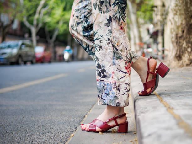 Close up on girl's feet wearing red sandals in the city, urban road background. stock photo
