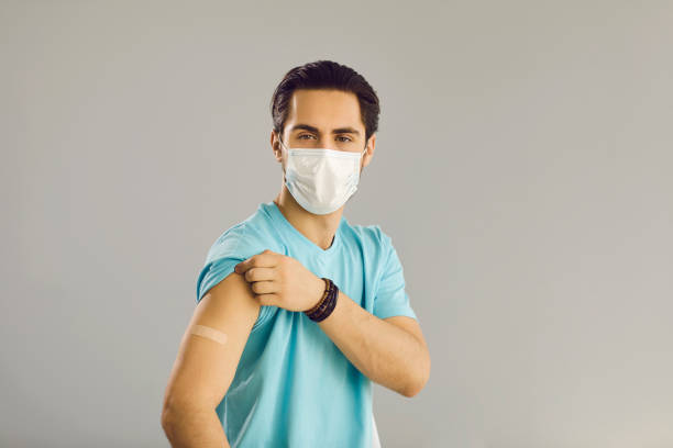 Close up on gray background man in medical mask shows hand with patch at vaccine injection site. stock photo