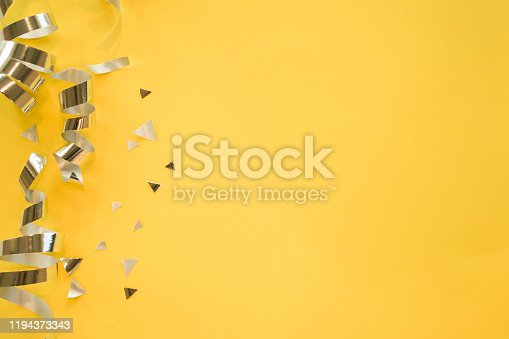 close up on group of silver color of rolling ribbon and confetti on yellow background with copy space for christmas festival happy new year ,carnival , birthday and anniversary, concept design