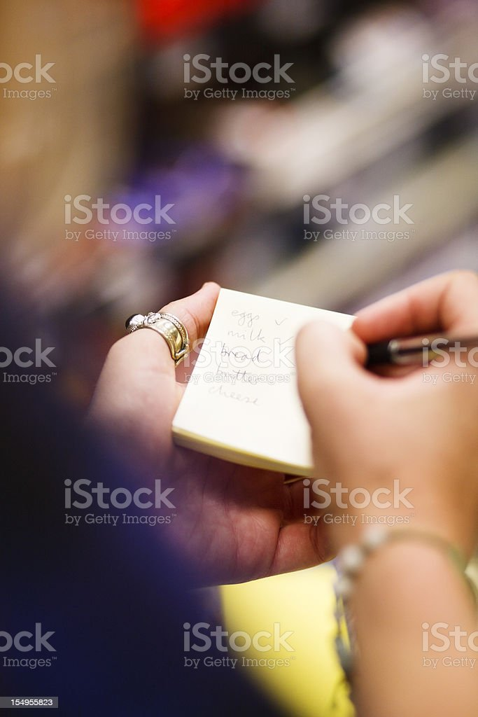 Close up on hands as woman checks shopping list stock photo