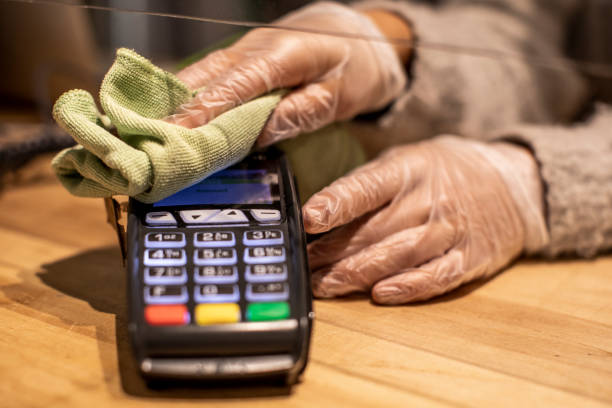 Close up on hands cleaning credit card reader.