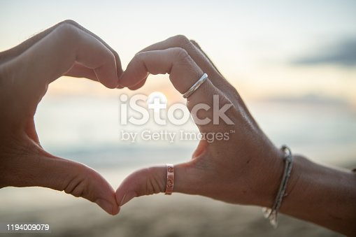 Young couple making a heart shape frame together on the beach  People love travel nature concept