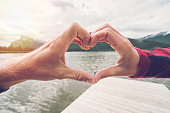 Young couple making a heart shape frame together on mountain lake landscape